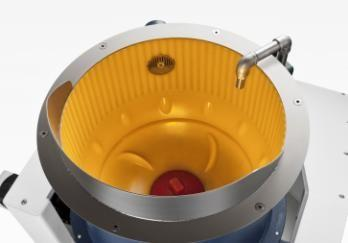 In the new TT-centrifugal disk finishing machines the gap (interface) between the (lower) rotating spinner and (upper) stationary work bowl is rinsed with process water