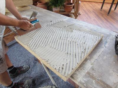 Um die Hanfabsorberplatte CapaCoustic Nature Platten an der Innenwand anzubringen, wird Caparol Klebe- und Spachtelmasse 190 vollflächig aufgetragen (Foto: Bernd Schamberger/Caparol)