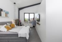 Auch im Schlafzimmer zieht sich der luftig-loftige Stil durch: Weiß, Grau und Anthrazit bilden die Hauptfarben, Akzente setzen die gelben Kissen (Foto: Caparol Farben Lacke Bautenschutz/Andrea Nuding)