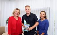 """Tim Bäßler least das hundertste JobRad bei CONET – Geschäftsführerin Anke Höfer (links) und Personalleiterin Sabine Cox überreichten ihm das Buch """"Die 100 schönsten Radtouren"""""""
