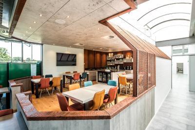 Spannende Werkstoffkombination: durch die Beton-Optik der Kücheneinrichtung, das Streckmetall in Corten-Optik und den Holzboden entsteht ein einzigartiger Look. Foto: Maks Richter