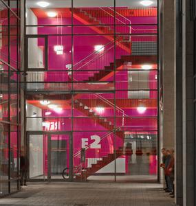 In der Abenddämmerung verleiht die Beleuchtung den roten und purpurfarbenen mit Amphibolin beschichteten Flächen in diesem Treppenhaus einen besonderen Charakter mit hohem Aufmerksamkeitswert, Foto: Caparol Farben Lacke Bautenschutz/Martin Duckek