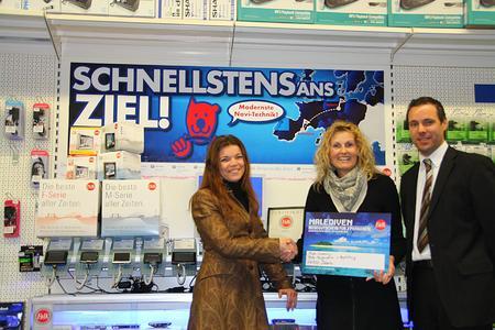 Heike Huber (Mitte) vom Euronics-Fachmarkt, Döbeln, nimmt den Gewinn freudestrahlend entgegen. Überreicht wurde er ihr von Susanne Hirth, Falk Trade Marketing Managerin (re.) und Jan Streubel, Falk Regional Sales Manager (li.).