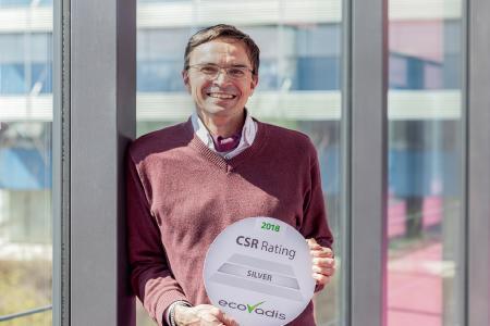 Stolz präsentiert Andreas Jenne, Sustainability Officer bei REHAU, die Silber-Auszeichnung der unabhängigen Rating-Agentur EcoVadis