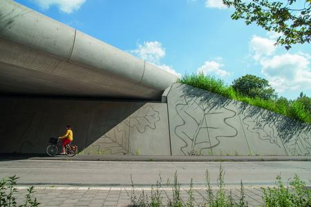 The abutments on the Ecoduct Zwaluwenberg between Utrecht and Hilversum in the Netherlands are designed to widen the bridge opening at the top. The abutment walls depict stylised oak leaves and acorns, realised with the NOEliner texture