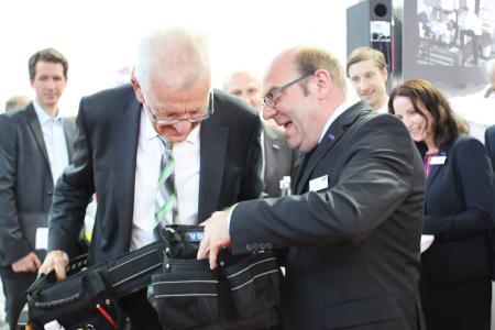 """VDWF-Präsident Professor Thomas Seul (r.) übergibt dem baden-württembergischen Ministerpräsidenten Winfried Kretschmann einen Gürtel für """"die anderen Werkzuege""""."""