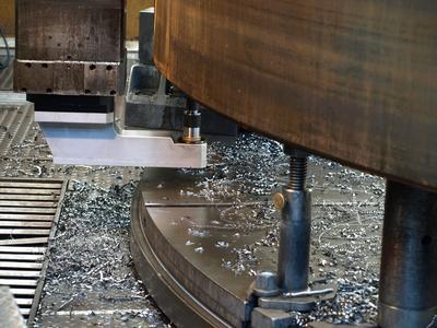 Erhöht in der Karusselldrehmaschine eingespannt können Bohrungen und Gewinde auch von unten in Stahlbauteile eingebracht werden, ohne die Spannsituation des Bauteils zu ändern