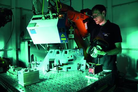 Markus Hofele, Doktorand am LaserApplikationsZentrum, richtet in der neuen Roboterzelle den 3D-Scanner aus. Der Bearbeitungskopf führt den Laserstrahl mittels beweglicher Spiegel über das Werkstück, Fotonachweis: © Hochschule Aalen/ Gaby Keil