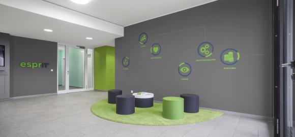 """Im Foyer des IT-Neubaus der DAW korrespondiert frisches Grün mit dunklem Grau. Die Piktogramme an der Wand stehen für """"emotionalize, empower, evolve, inspire, perform, professionalize"""". Ihre runde Form wiederholt sich in Teppich und Sitzhockern (Foto: Caparol Farben Lacke Bautenschutz/Blitzwerk.de)"""
