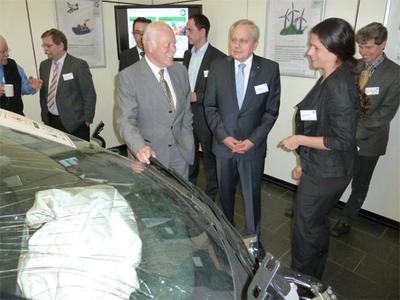 Prof. Klaus Langwieder, Mitglied im Programmausschuss, und der Vorsitzende der crash.tech Dr. Lothar Wech diskutieren das Ergebnis des Crashversuchs eines i3 mit der BMW-Crashexpertin Izabella Ferenczi