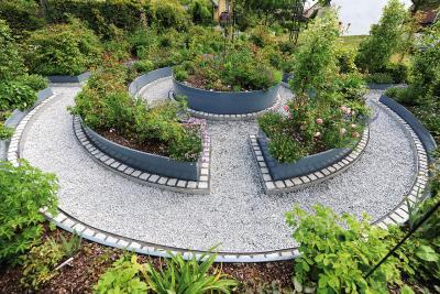 Insgesamt fünf radiale Hochbeete bilden ein kreisrundes sowie begehbares Labyrinth und gleichzeitig eine blühende Oase, an der sich die Bewohner lange Zeit erfreuen können.