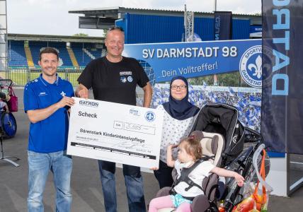 Oliver Keller, Vertriebsleiter SV Darmstadt 98, Dr. Arne Brüsch, Vorstandsvorsitzender der DATRON AG und Anja Boutbel von der Bärenstark Intensivpflege mit dem Spendenscheck über € 5.555 für die Initiative Bärenstark aus Darmstadt.
