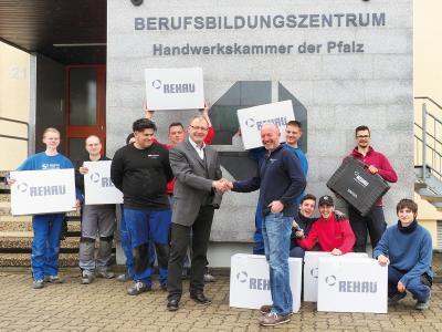 Gemeinsam mit Auszubildenden der Handwerkskammer der Pfalz freuen sich Erik Schehl (6.v.r.), Leiter der außerbetrieblichen Ausbildung bei der Handwerkskammer der Pfalz, und Norbert Reisinger (6 v.l.), Außendienstmitarbeiter beim Polymerexperten REHAU im Verkaufsbüro Frankfurt, über die REHAU Spende von zwölf Werkzeugeinheiten RAUTOOL für die Installation von Trinkwasser- und Heizungsrohrsystemen, Foto: Handwerkskammer der Pfalz