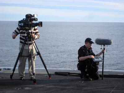 """Mike Nunan, CTV Post-Production Supervisor, bei Aufnahmen für einen Dokumentarfilm mit Neumann-Digitalmikrofonen auf dem """"audio-feindlichen"""" Flugdeck der USS Nimitz, einem Flugzeugträger der U.S.-Marine."""
