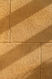 Die 45 mm dicke Absorberplatte aus Hanf CapaCoustic Nature wird direkt auf das Mauerwerk vollflächig verklebt. Sie nimmt den Schall in den Pflanzenfaserstrukturen und -poren auf (Foto: Caparol Farben Lacke Bautenschutz/Martin Duckek)