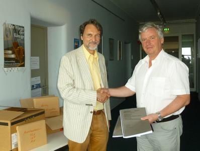 Prof. Dr. Rolf Pohl (rechts) überreicht dem Dekan des Fachbereichs Betriebswirtschaft, Prof. Dr. Gunter Kürble, die Akkreditierungsunterlagen