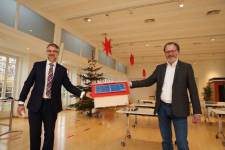 WEMAG-Vorstand Thomas Murche (li.) überreicht dem Geschäftsführer der Diakoniewerk Neues Ufer gGmbH Thomas Tweer symbolisch für die Kindertagesstätten im Netzgebiet das Geschenk der diesjährigen Kita-Weihnachtsaktion