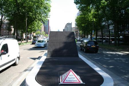 Notausgang der Metro Amsterdam an der U-Bahnstation Weesperplein: Oberirdisch gesehen eine unauffällige Verkehrsinsel mit einem horizontal über dem Ausstieg befindlichen Absperrgitter mit einer beachtlichen Masse von 4.859 kg