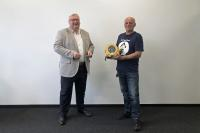 Stryker spendet Mitarbeiter der MC-Bauchemie einen Defibrillator: Hans-Peter Marten (l.) überreichte Mieczyslaw Pacanowski (r.), Pförtner bei der MC-Bauchemie, einen Defibrillator.