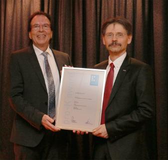 Kai-Uwe Reiß von pro-K überreicht Thomas Sauer, Leiter Entwicklungsbereich B und Elektronik bei ebm-papst, die Urkunde.