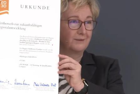 Theresia Bauer, Ministerin für Wissenschaft, Forschung und Kunst Baden-Württemberg, hält die Prämierungsurkunde für die Region Heilbronn-Franken während des Live-Streams in die Kamera