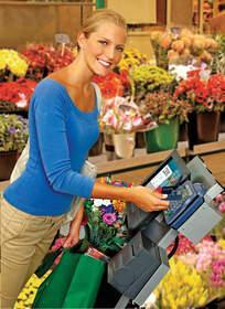 A shopper pays for flowers quickly and easily through the IBM AnyPlace Checkout, which is strategically placed in the florist department of a large retail operation