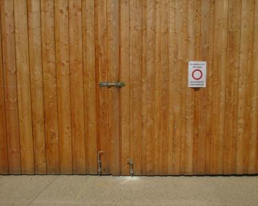 Durch Holztor geschützter Eingangsbereich zu einer Unterkunft für Asylbewerber