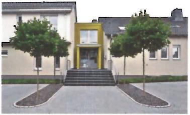 """Eine Mini-Allee führt zum tundragrünen Eingangsbereich der IT-Firma """"GreenGate"""" (30 Tundra 125). Er verbindet das frühere alte Pfarrhaus (rechts) mit dem repräsentativen Neubau / Foto: Caparol"""