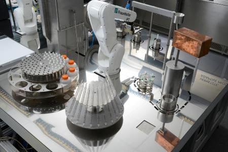 Two industrial jointed-arm robots inside the system assist the fully end-to-end automated cell production.