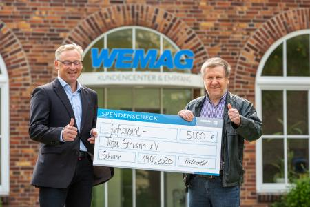 WEMACOM-Mitarbeiter Thomas Pätzold (li.) hat über die Crowdfunding-Plattform der WEMAG Spenden eingesammelt, die er nun dem Vorsitzenden der Schweriner Tafel, Peter Grosch, symbolisch überreichen konnte (Foto: WEMAG/Stephan Rudolph-Kramer)