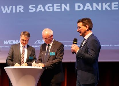 WEMAG-Vorstand Thomas Murche (l.) und LFV-Präsident Joachim Masuch (m.) zeichnen den Kooperationsvertrag in Gegenwart des NDR-Sportchefes und Moderator Clemens Paulsen (r.) (Foto: WEMAG/Diana Kuhrau)