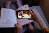 Familie liest 3D Buch mit AR