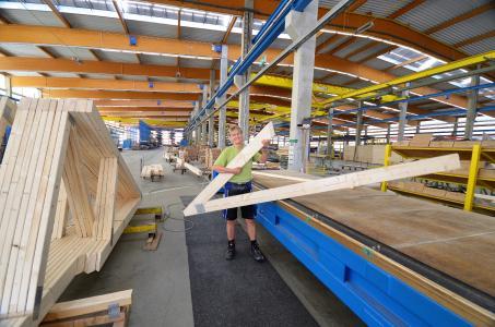 Bianca Bäker ist gelernte Bautischlerin und arbeitet seit über elf Jahren in der Produktion bei Opitz Holzbau in Neuruppin. Bei der Herstellung von Nagelplattenbindern ist der routinierte Umgang mit Maschinentechnik für sie geübte Praxis. Foto: Achim Zielke für OPITZ Holzbau/GIN, Ostfildern; www.nagelplatten.de