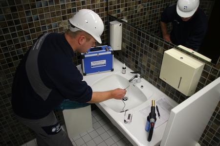 Mitarbeiter prüft Trinkwasser auf Legionellen-Belastung