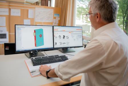 SOLIDWORKS Arbeitsplatz in der Konstruktion von AMF. Die zwei Bildschirme erlauben die gleichzeitige Darstellung von CAD- und PDM-Daten
