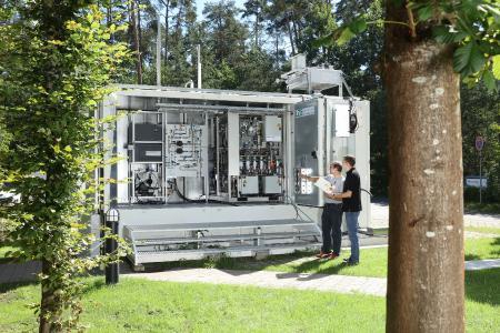 Mitarbeiter des LZE-Projekts diskutieren den kompakten verfahrenstechnischen Aufbau des innovativen Energiespeichersystems.