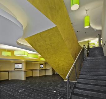 Die goldenen farbakzente an den treppenaufg ngen im cinedom singen harmonieren mit den - Architektengruppe numerobis ...