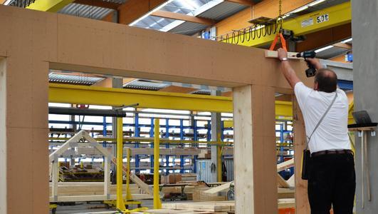 Parallele Fertigung: Komplett wärmegedämmte Holztafelwände (Vordergrund) können in der Opitz Zukunftsfabrik in Neuruppin zeitgleich mit robusten Nagelplattenbindern für das Dachtragwerk (Hintergrund) hergestellt werden. Die Kapazitäten haben längst Industrieniveau erreicht und sind mit einem normalen Handwerksbetrieb nicht mehr zu vergleichen. (Foto: Achim Zielke für Opitz Holzbau, Neuruppin; www.opitz-holzbau.de)