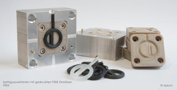 Abbildung 1: PEEK Formeinsätze mit Gussteilen aus ABS(schwarz) und Polyurethan(transparent)