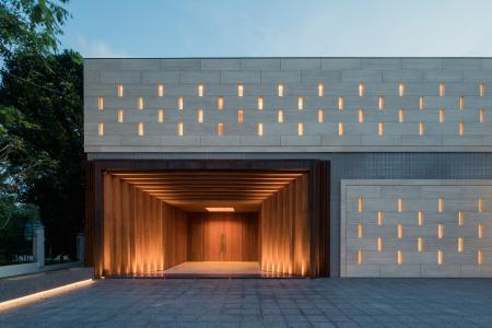 Die mit Travertinplatten verkleidete, dezent perforierte Haupteingangsfassade befindet sich auf der Straßenseite. Unterhalb der Eingangsebene sind sekundäre Nutzungsbereiche, u. a. eine Tiefgarage, untergebracht. Bildnachweis: Khoo Guojie, Singapur