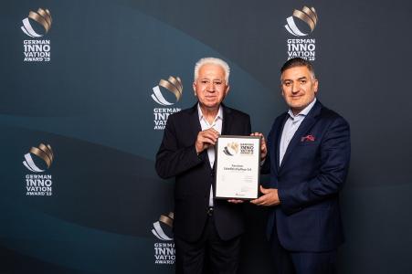 """Dr. Ismail Özkanli (r.) und sein Vater Hüsnü Özkanli (l.) nehmen den  """"German Innovation Award"""" entgegen"""