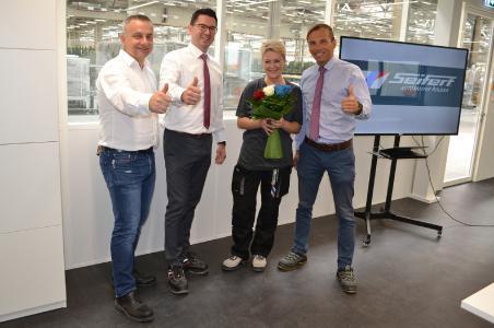 Brygida Rzeszutek (zweite von rechts) ist die 2.000 Mitarbeiterin der Seifert Logistics Group. Zur Begrüßung am neuen Arbeitsplatz in Jawor überreichten ihr (von links) Marek Dziejak (Lagerleitung, Seifert Automotive Polska), Simon Szczepanik (Prokurist, Seifert Automotive Polska), sowie Michał Musielak (Niederlassungsleiter, Seifert Automotive Polska) einen Blumenstrauß in den Farben der Logistik-Gruppe.