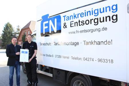 Wilfried Wöltje (l.) überreicht das Gütesiegel der Berufsgenossenschaft Holz und Metall an Florian Nuttelmann. (Quelle: Sylvia Wendt/Kreiszeitung)