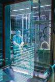 Der Blick in die Impfstoffabfüllung ist bei laufender Produktion nur hinter der Glasscheibe möglich. Die Mitarbeiter Björn Dalichau und Andreas Müller bereiten die Linie für die Abfüllung des SARS-CoV-2-Impfstoffkandidaten vor