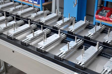 Taktkettenumlauf für den Transport von Getriebegehäusen zwischen zwei Bearbeitungszentren. Die Gehäuse werden per Roboter aufgesetzt und abgenommen. Zwei Querprofile mit Aufnahmezapfen werden zu einem Werkstückträger kombiniert