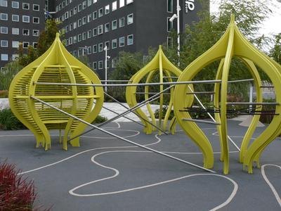 Wie Kunstobjekte wirken die gelben Klettergerüste des Spielbereichs auf dem Dach.