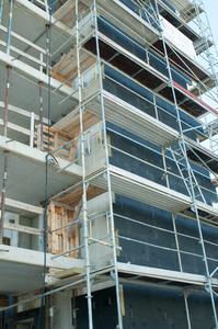 Fassade des Versorgungsturms . Die 100-mm-starke vlieskaschierte Dämmung ist in den unteren Etagen bereits angebracht. Der Untergrund ist Beton. (Foto: Ejot)