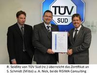 R. Seidlitz von TÜV Süd (re.) überreicht das Zertifikat an S. Schmidt (Mitte) u. A. Nick, beide RISIMA Consulting