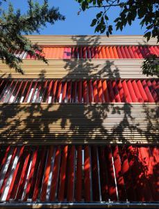 Großlamellengruppen in roten RAL-Tönen kennzeichnen den zweiten Flügel des Gebäudes. Zum Einklemmschutz wurden die Lamellen über das Schüco Sonnenschutz-Steuerungs-system so programmiert, dass sie nicht komplett zuklappen / Foto: Schüco International KG