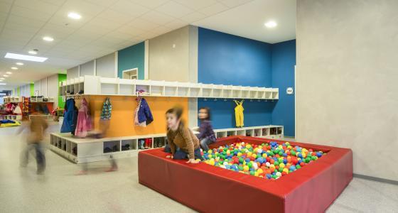 Der Flur wird als Spielfläche genutzt, die bunten Garderobenmodule dienen als Raumteiler. Die Farbakzente der Wände kennzeichnen nicht nur die Gruppenräume, sondern beleben auch die Flurszenerie (Foto: Caparol Farben Lacke Bautenschutz/Martin Duckek)